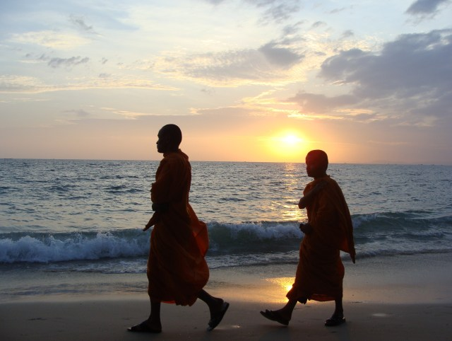 Two young monks walk across the sandy beach of Independence Bay as the sun sets in Sihanoukville, Cambodia.